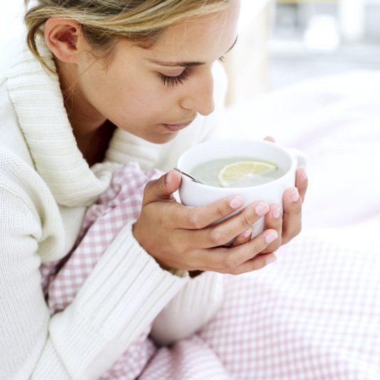 простуды: девушка держит чашку чая с лимоном